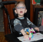 Young Boy Coloring in Wheel Chair
